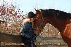 Девушка подростка и лошадь залива обнимая один другого Стоковые Фото