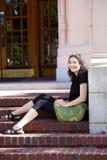 Девушка подростка наслаждаясь солнечностью, сидя на кирпиче шагает outdoo Стоковые Фото