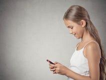 Девушка подростка отправляя СМС на сотовом телефоне