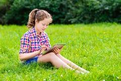 Девушка подростка сидя на траве с цифровой таблеткой Стоковое Изображение RF