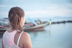 Девушка подростка смотря в расстояние на тропическом пляже на заходе солнца во время летних отпусков Стоковое фото RF