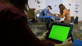 Девушка подростка swiping ПК таблетки сидя на столе в классе и мальчике девушка сидя на другом столе акции видеоматериалы