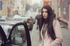 Девушка получает в автомобиль Она одета в пальто Стоковое Фото