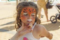 Девушка получая ее сторону покрашенный путем красить художника Стоковая Фотография
