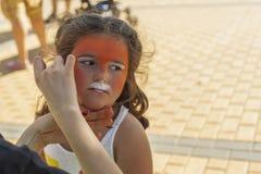 Девушка получая ее сторону покрашенный путем красить художника Стоковая Фотография RF