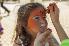 Девушка получая ее сторону покрашенный путем красить художника Стоковое фото RF