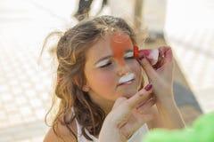 Девушка получая ее сторону покрашенный путем красить художника Стоковые Изображения RF
