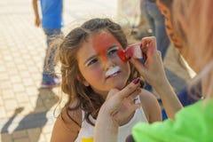 Девушка получая ее сторону покрашенный путем красить художника Стоковые Изображения