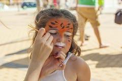 Девушка получая ее сторону покрашенный путем красить художника Стоковые Фото