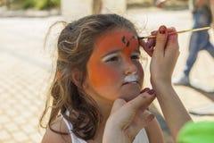 Девушка получая ее сторону покрашенный путем красить художника Стоковое Изображение