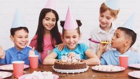 Девушка празднуя день рождения и делая желание дома стоковая фотография rf