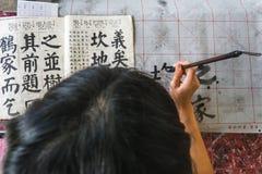 Девушка практикуя китайское callingraphy Стоковые Изображения