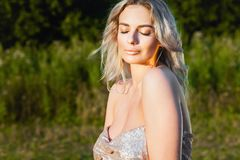 Девушка представляя в поле на заходе солнца Стоковое фото RF