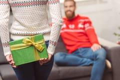 Девушка представляя подарок рождества к парню Стоковое фото RF