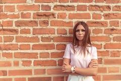 Девушка представляя против предпосылки старой красной кирпичной стены Открытый космос для текста Серьезный взгляд В лете в городе стоковое изображение rf