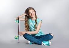 Девушка представляя при скейтборд сидя в студии Утеха, улыбка, положительные эмоции стоковое фото