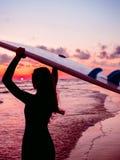 Девушка прибоя с длинными волосами идет к серфингу Силуэт женщины с surfboard на пляже на заходе солнца или восходе солнца Серфер Стоковое Изображение