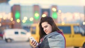 Девушка привлекательного коричнев-с волосами gorgeus милая используя белый телефон в городской улице города весной, несосредоточе видеоматериал