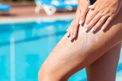 Девушка прикладывает сливк предохранения от солнца с ее руками на ее загоренной ноге бассейном на горячий летний день Фактор пред стоковое фото rf