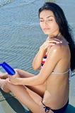 Девушка прикладывая лосьон suntan Стоковые Изображения