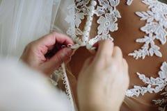 Девушка прикрепляет платье свадьбы на задней части невесты конец вверх стоковое фото