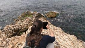Девушка принимает видео как небольшие волны бьют красиво на утесах на пляже сток-видео