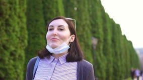 Девушка принимает медицинскую маску от ее стороны и глубоко вдыхает воздух в парке, медленном mo акции видеоматериалы