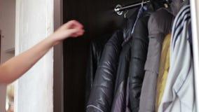Девушка принимает пальто осени от шкафа дома видеоматериал