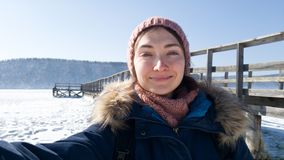 Девушка принимает selfie против деревянной пристани Река Angara зимы Путешествие зимы через Сибирь стоковая фотография