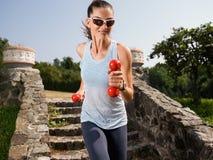 Девушка приниманнсяые за гантели фитнеса Стоковые Изображения RF