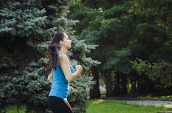 Девушка приниманнсяый за фитнес в парке, делая тренировки Тренировка на улице в утре лета Спорт концепции здоровый стоковое фото rf