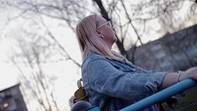 Девушка принимансяа за имитатору для идти на выравниваясь спортивную площадку в парке города акции видеоматериалы