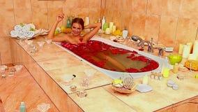 Девушка принимая ванну с лепестками розы Промежуток времени видеоматериал