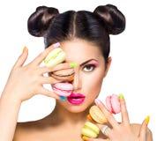 Девушка принимая красочные macaroons Стоковые Фото