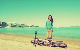 Девушка при велосипед отдыхая на пляже Стоковые Фотографии RF
