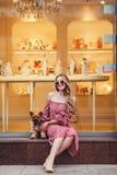 Девушка при ее собака сидя около мола Стоковая Фотография