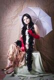 Девушка при зонтик и горжетка представляя в студии стоковое изображение