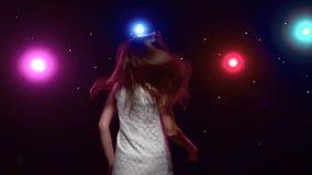 Девушка при длинные волосы завихряясь против диско освещает движение медленное акции видеоматериалы