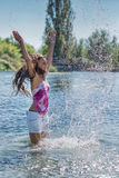 Девушка при длинные волосы играя с водой Стоковые Фото