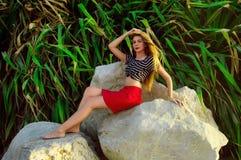 Девушка при длинные волосы сидя на больших камнях Стоковая Фотография RF