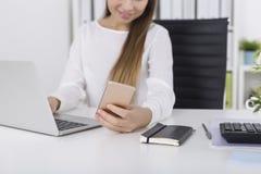 Девушка при длинные коричневые волосы смотря телефон Стоковые Фото