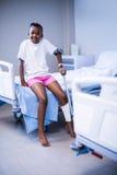 Девушка при костыли сидя на больничной койке в палате стоковые фотографии rf