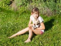 Девушка при кролик сидя на луге стоковые изображения