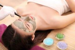 Девушка при лицевая маска лежа в спа-центре здоровья красоты Стоковое фото RF