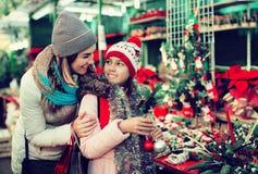 Девушка при мать выбирая флористическое украшение Стоковые Изображения RF