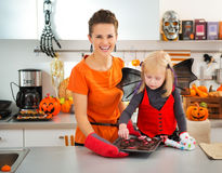 Девушка при мать держа поднос с печеньями хеллоуина в кухне Стоковая Фотография RF