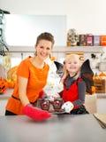 Девушка при мать держа поднос с печеньями хеллоуина в кухне Стоковые Изображения RF