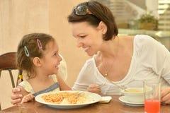 Девушка при мать есть на таблице Стоковое фото RF