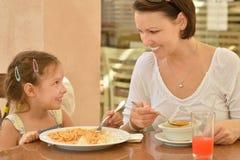Девушка при мать есть на таблице Стоковые Фотографии RF
