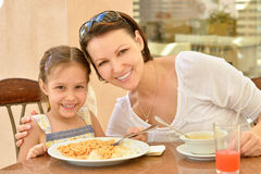 Девушка при мать есть на таблице Стоковое Изображение RF